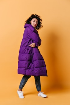 Full length view of young woman in long down jacket