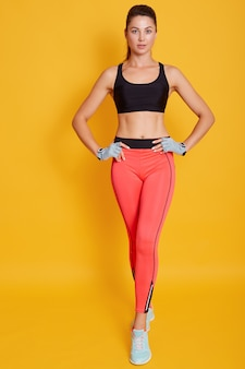 Full length woman, body of fit female wears sports bra and leggins, shows slim belly and press, isolated on yellow wall. diet, fitness and healthy lifestyle concept.