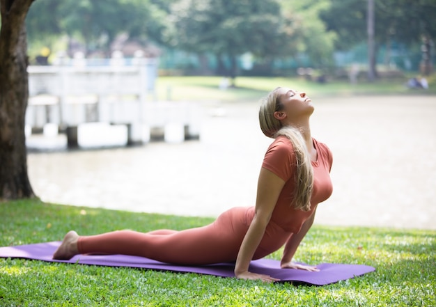 Full length of woman exercising on mat at park