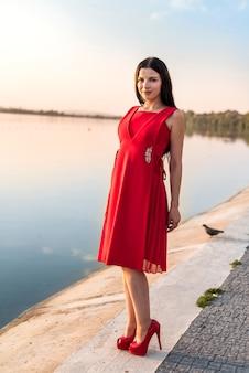 日没のビーチに立っている長いドレスの全身女性