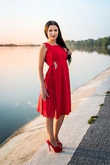 日没のビーチに立っている長いドレスを着た全身の女性