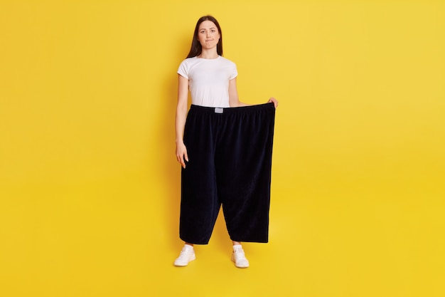 Full length young adult caucasian girl wearing casual t shirt and too big size pants, looks at camera with puzzled expression and bewilderment, purses lips, isolated over yellow wall.