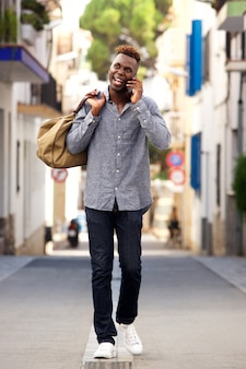Full length young african male traveler walking outdoors and talking cell phone