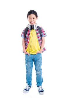 Full length of young asian boy standing and smiling over white background