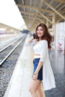 Full length young asian woman standing and looking at camera while waiting in train station