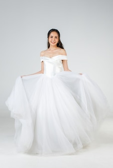 Full length of young attractive asian woman, soon to be bride, wearing white wedding gown looking happy spinning. concept for pre wedding photography.