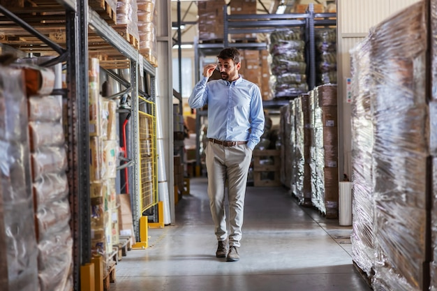 Full length of young attractive ceo walking trough warehouse and checking on goods.