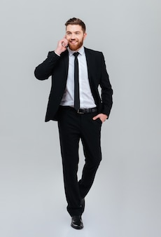 Full length young bearded business man in black suit moves with hand in pocket and talking at phone in studio isolated gray background