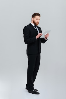 Full length young bearded business man in black suit standing sideways and writing message on tablet computer isolated gray background