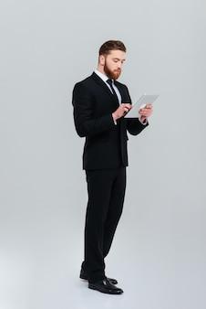 검은 양복을 입은 전체 길이의 젊은 수염 사업가가 옆으로 서서 태블릿 컴퓨터 격리된 회색 배경에 메시지를 작성합니다.