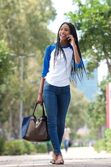Full length young black woman walking in the city and talking on cell phone