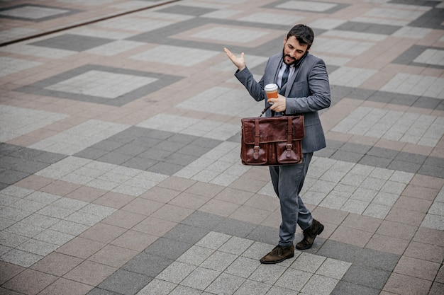 Full length of young businessman going to work and having phone conversation.