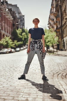 Full length of young female in casual clothes standing on the road and looking at