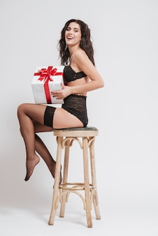 Full length of a young laughing woman in black lingerie with stockings holding gift box and sitting on a chair isolated
