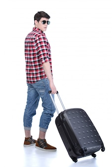 Full length of young male tourist standing with suitcase.