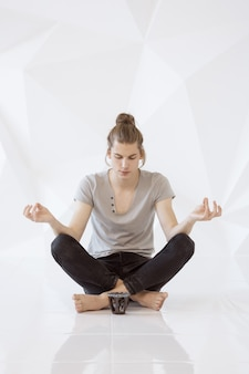 Full length of a young man meditating in lotus position against white polygon background