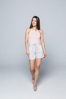 Integrale di giovane ragazza sexy di bellezza che cammina sui tacchi alti isolati sulla parete bianca.