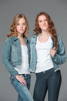 Full length of young slim female girl in denim jeans on gray