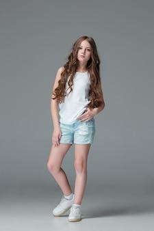 Full length of young slim female girl in denim shorts on gray background