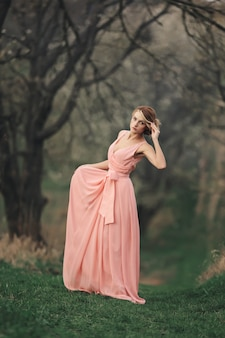 Full length young stylish woman near blossoming tree in the spring park. blonde girl with hairstyle in pink dress