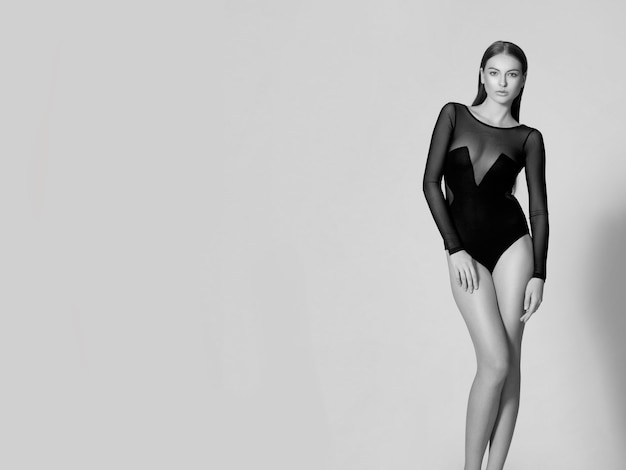 Full length of a young woman in black bodysuit.