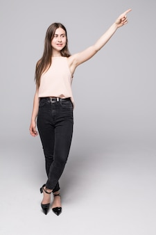 Full length of young woman pointing to the side and looking there, isolated on white wall