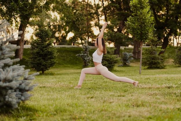 공원에서 자연 속에서 요가를 하는 전신 젊은 여성, 삶을 회복하고 속도를 늦추는 개념.