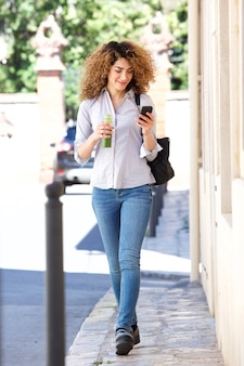 Full length young woman walking in city with mobile phone and juice