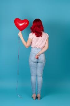 빨간 머리를 가진 전체 길이 젊은 여자는 그녀를 다시와 서 그녀의 손에 빨간 풍선을 보유