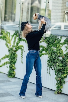 Полная длина молодая светловолосая мода и 0 кавказская женщина держит маленькую забавную собачку на руках двух цветов - черного и белого чихуахуа. обнимает и целует любовь. веселые эмоции.