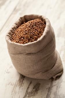 Полноценный льняной мешок с гречкой в деревянный настил.