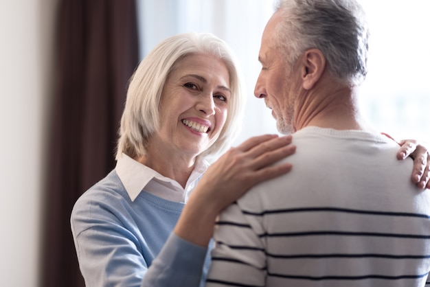 Full of love and care. delighted smiling aged couple dancing at home while hugging each other and expressing happiness