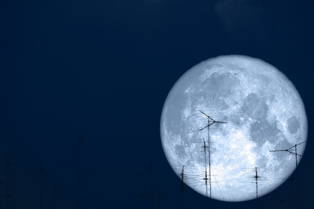 Full milk moon back on silhouette antennas on the night sky