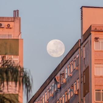Full moon over a building on botafogo beach in rio de janeiro brazil