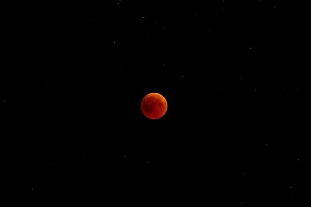 Затмение полнолуния. спутник земли ночью против неба со звездами.