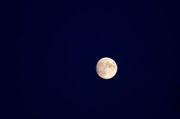 Полная луна на фоне голубого неба