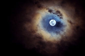 Full moon on cloudy day.