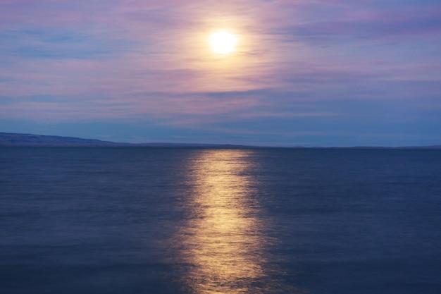 Full moon rising above mountain lake
