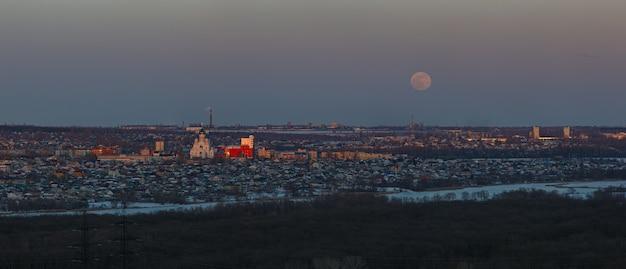 Полная луна поднимается над городом. время заката в сумеречном небе. панорамный вид на православную церковь.