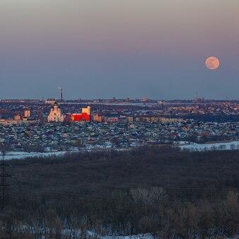 Полная луна поднимается над городом. время заката в сумеречном небе. вид на православную церковь.