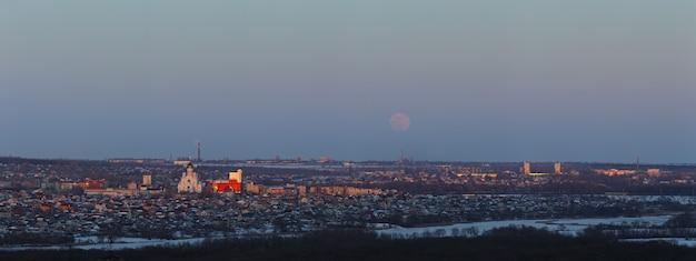 Полная луна поднимается над городом