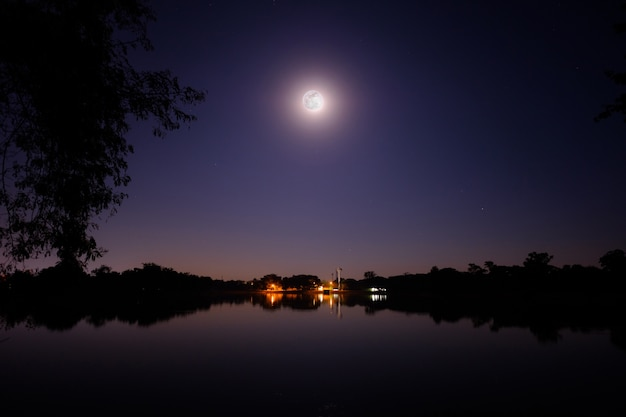 Full moon shine bright in the night above the big lake and small village