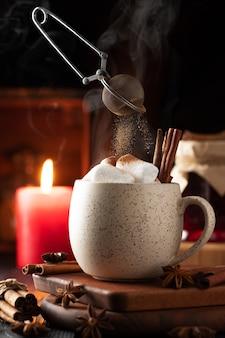 ホットチョコレートとマシュマロのマグカップ一杯、そしてシナモンがふるいからマシュマロに注がれます