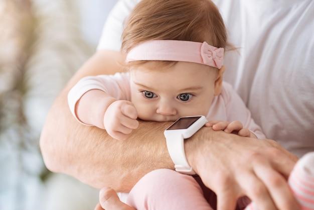 관심 가득. 아버지의 손에 누워 관심과 기쁨을 표현하면서 멀리보고 달콤한 귀여운 관련 아기 소녀
