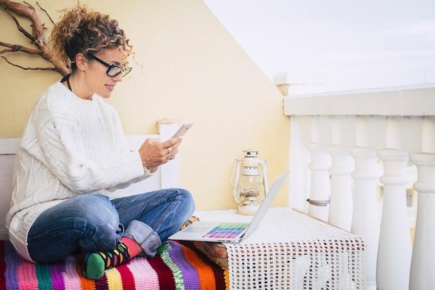 テラスで屋外のノートパソコンで自由に働く中年女性のカラー画像がいっぱい、背景には古いビンテージランプがあり、別の種類のオフィスが独立して働く