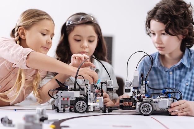 クリエイティブなアイデアがいっぱい。プロジェクトに取り組んでいる間、クラスに座ってロボットを構築する才能のある集中したポジティブな子供たち
