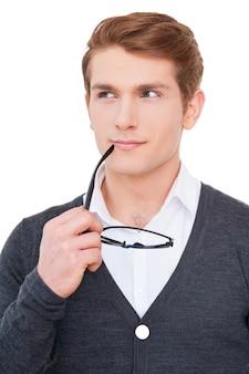 クリエイティブなアイデアがいっぱい。思いやりのある若い男は、口の近くに眼鏡を保持し、白で孤立して立っている間目をそらします