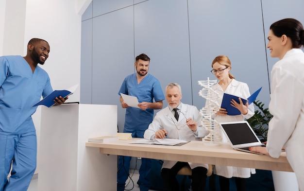 好奇心旺盛。微生物学とdnaモデル構造を説明しながら、医学部の学生に働き、講義をしている、うれしい古い経験豊富なメンター