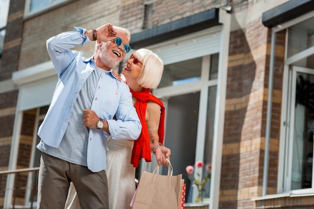 Полный эмоций. позитивная модная пожилая пара, приятная прогулка после покупок, держа свои покупки в руках