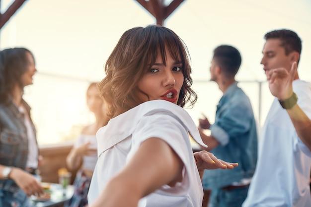 힘이 가득 찬. 흰 셔츠를 입은 예쁘고 젊은 여성이 친구들과 옥상 테라스에 서서 춤을 추고 카메라를 바라보고 있습니다. 파티 개념입니다. 우정